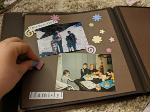 Hand placing decorations in scrapbook with brown page for the Supplies section in the Legacies that Last: Preserving Your Memories with Legacy Scrapbooks and Heirloom Albums post on the Legacy Estate Planning Blog. Image credit to Heather Agun