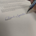 Hand signing a document for 3 major motivators for estate planning blog post at Legacy Estate Planning